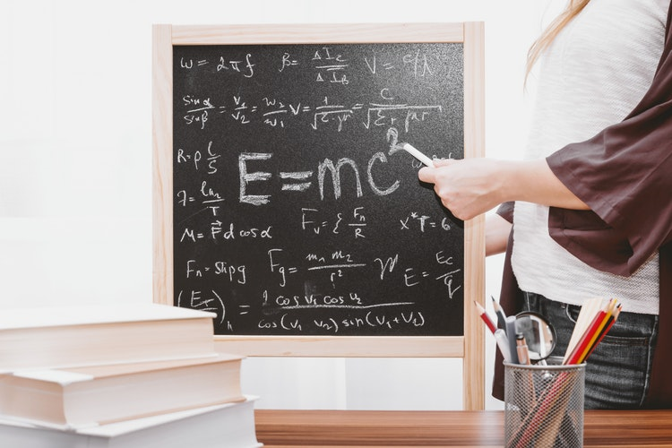 woman writing on a chalkboard, E=mc2
